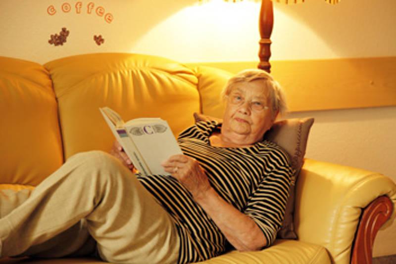 Seniorin liegt mit einem Buch auf dem Sofa