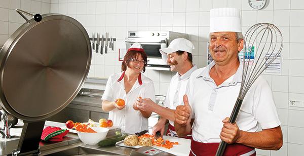 Koch mit Mitarbeitern in der Pflegeheimküche