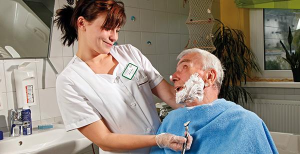 Pflegerin mit Senior beim Rasieren